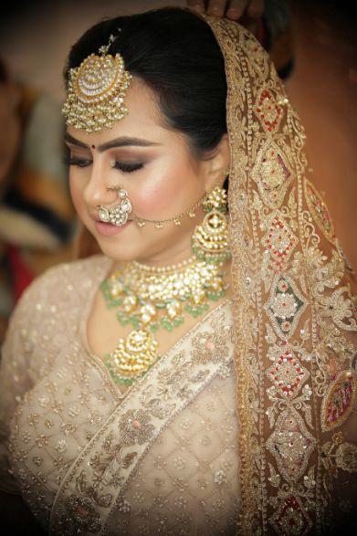 bridal bu , floral bridal bun, indian wedding indian bride , punjabi bride , peplum top | peach lehenga | Punjabi wedding