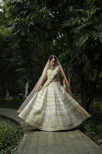 beautiful bridal lehenga in gold and ivory | brides twirling shots | Intimate Wedding in Jim Corbett