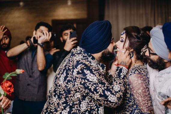 sealing it with a kiss | indian wedding candid photography | Sparkling Red Gown for the Cocktail