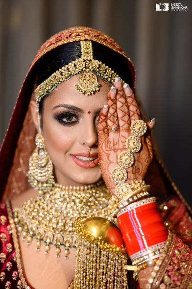 red chooda for the bride | gold jewellery designs for the bride | Sabyasachi Lehenga in Maroon