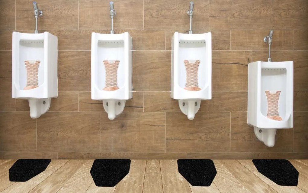 Mango Splash Hog Vertical Urinal Screens With Black Original Cut Antimicrobial Urinal Mats From WizKid Products Installed In A Public Restroom