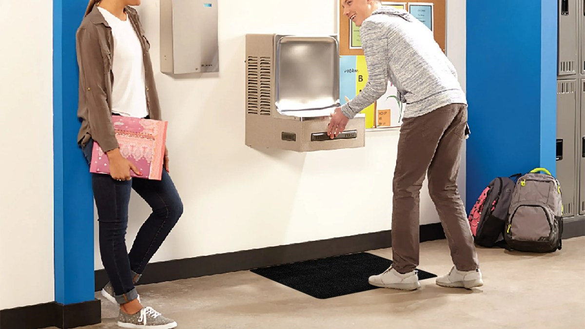 Boy And Girl At Drinking Fountain With WizKid Products Antimicrobial Runner Mat Below Drinking Fountain In School Building