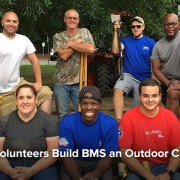 Lowe's Volunteers in a group photo smiling before getting ready to build the outdoor classroom