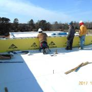 Framing and sheathing the Unit A roof parapet so that the roof membrane can be terminated. Gym roof can be seen towards top of photo