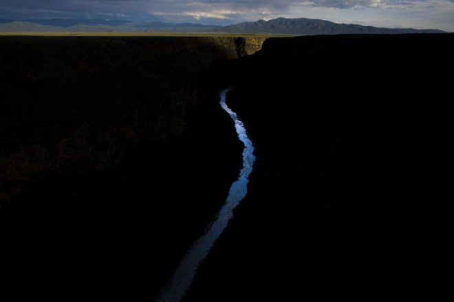 The Rio Grande reflects the sky as it twists down the canyon towards the Sangre de Cristo mountains in Northeastern New Mexico.