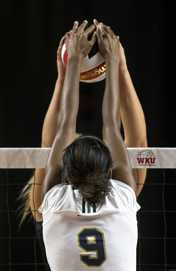 Florida International University sophomore middle blocker, Brianna Gogins, (9) attempts to block a hit by Western Kentucky University sophomore setter, Jessica Lucas, (1). The Lady Toppers defeated the Panthers in the first three sets. JAKE POPE