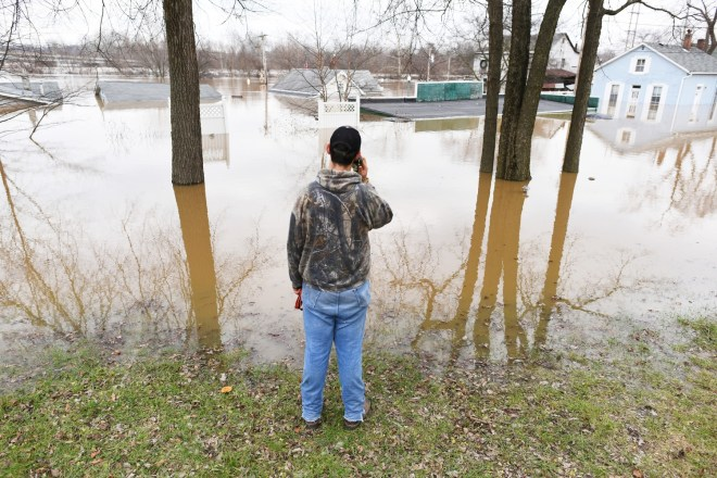 Dawson Newbold,16, of Housespring makes a call while taking a break from sandbagging on December 30, 2015 in Fenton, Missouri. The Meramec river is expected to crest at 43 ft late Wednesday.   Michael Noble Jr.