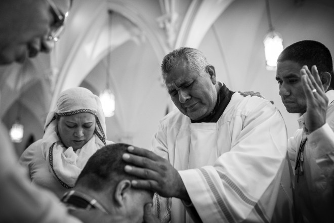 A man cries on the altar of St. Joseph's Church as Spanish-speaking members of the congregation lay hands on and pray for him during the Adoration of the Blessed Sacrament on Saturday, Oct. 8, 2016. | Photo by Gabriel Scarlett