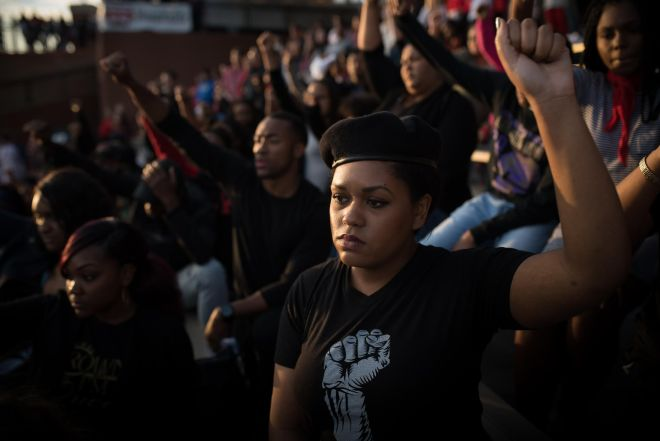 """Lydia Billion, a WKU alumnus, quietly kneels during the """"National Anthem"""" as a form of peaceful protests of the current treatment of African-Americans in the United States. Last weekend when students and members of the Major Redz knelt during the song, fellow fans attempted to shout them down. The protests were also spurred on by two recent incidents of racism on Western Kentucky University's campus. 