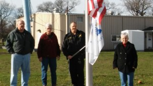 Council Member Tim Cummins, Council President Wendy Hoppe, Town Marshal Doug Vessely and Clerk-Treasurer Donna Henry prepare to raise Indiana's Bicentennial Flag.