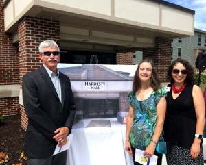 Jim Hardesty's nephew, Chuck Hardesty, niece, Joan Hardesty, and SCCF Director of Development, Sarah Origer, stand with an artistic rendering of the sign for Hardesty Hall, which will soon grace the dorm's entrance.