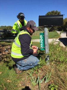 Kankakee Valley REMC employees Eric Duttlinger and Kristi Fricke complete the installation of a reflective mailbox sign for a member in Starke County. Over 300 reflective signs were installed on Oct. 14 for Community Day.