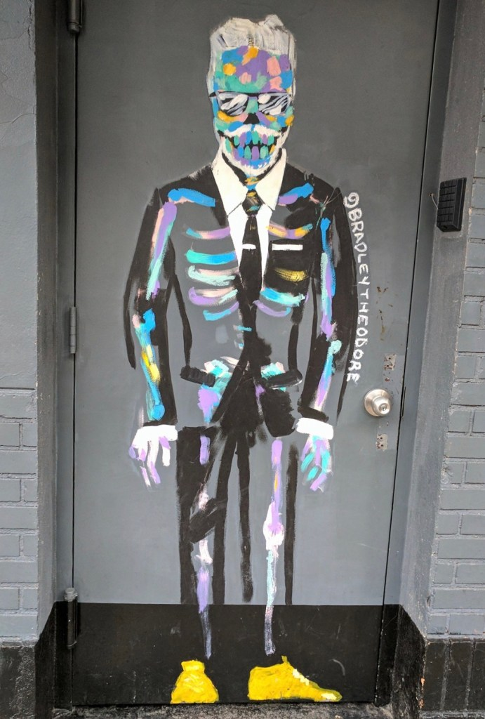 A Bradly Theodore skeleton in bold colors wearing a dark suit and tie, with yellow shoes and sunglasses. Street art that survived.
