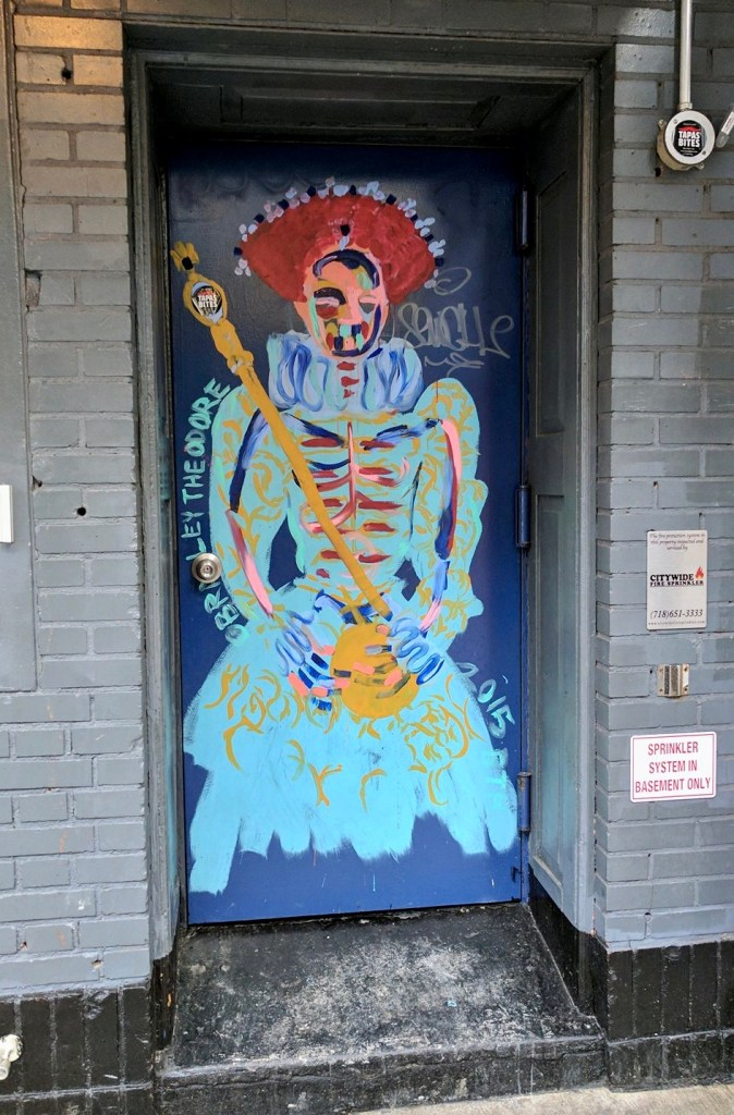 A Bradley Theodore skeleton Queen in bold colors waits to receive you in the recessed door. Street art that survived.
