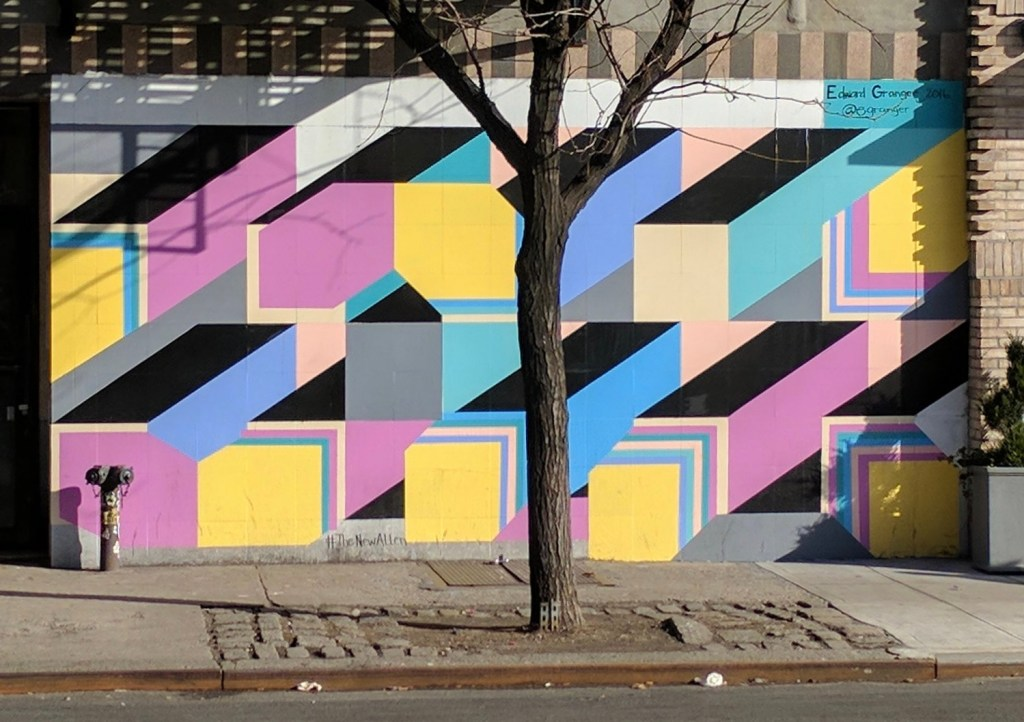A section of wall with square columns bursting from top right to bottom left in layers. Alternating pastel colors, topped with black. Street art that survived.