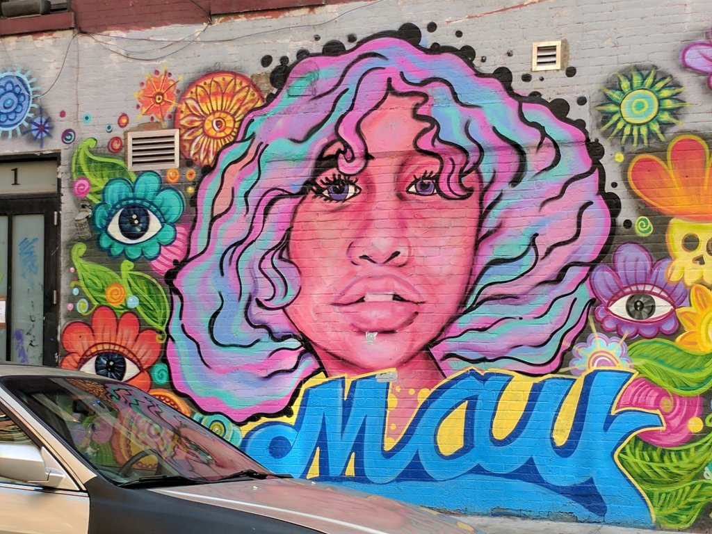 "Cartoon Colorful face of a woman surrounded by eyes, flowers, leaves and the word ""May"""