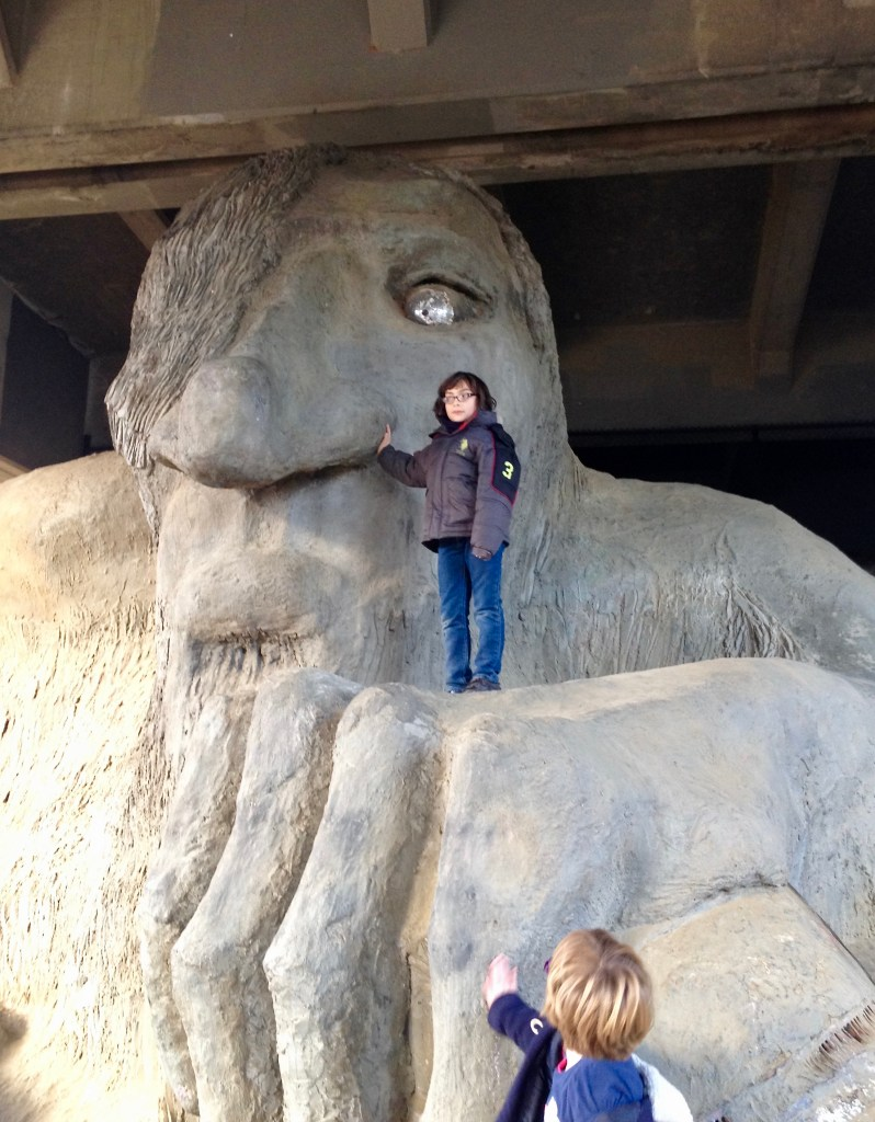Close up of the Fremont Troll being climbed by two boys.