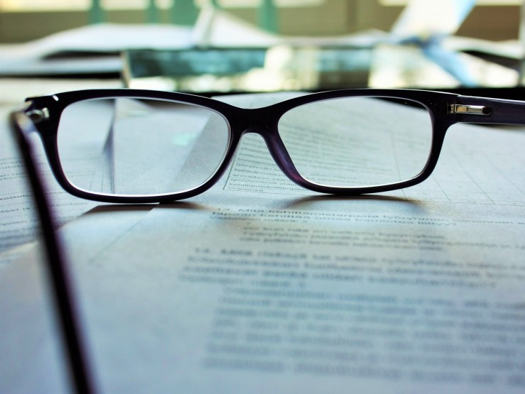 glasses sitting on top of paperwork