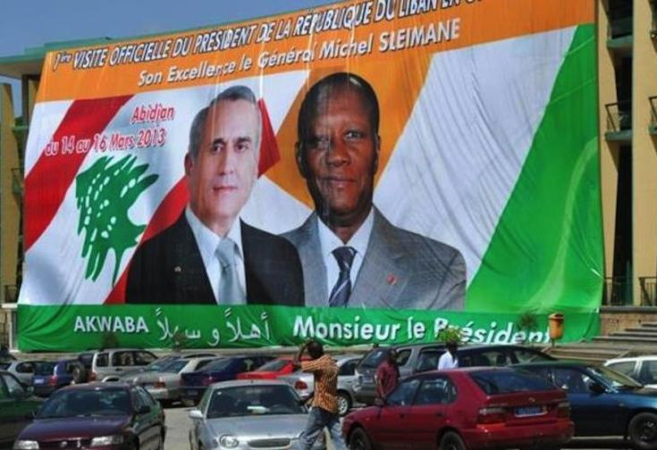 People walk on March 12, 2013 past a poster bearing the portraits of Ivory Coast President Alassane Outtara (R) and his Lebanese counterpart Michel Sleiman on the Republic Square in Abidjan. AFP/Sia Kambou