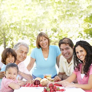 Three Generation Hispanic Couple Enjoying Picnic In Park
