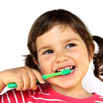 Little Smiling Curly Girl Brushing Teeth Portrait