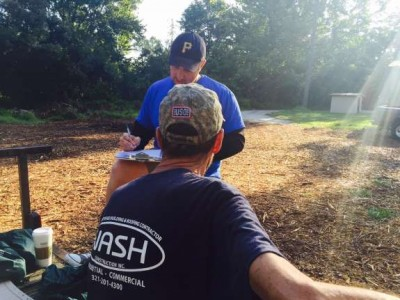 A volunteer gets information from a homeless veteran camping in the woods in Bithlo./Photo: Catherine Welch