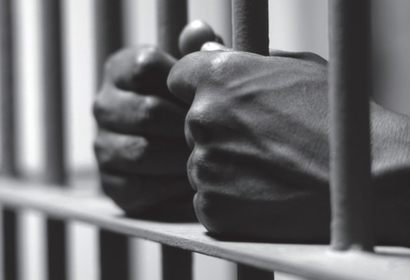Picture of a man's hands gripping prison bars