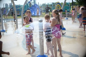 Four kids smiling and playing at the splash pad