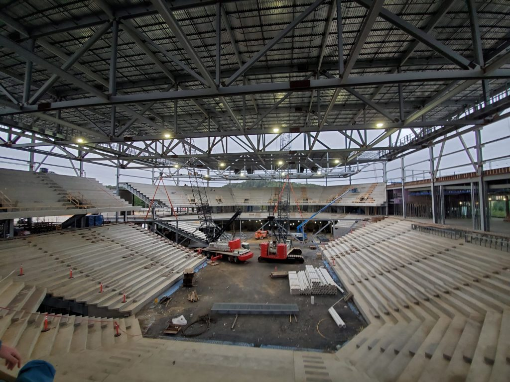 A wide-angle view of an indoor arena under construction