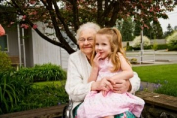 Grandmother in wheelchair with granddaughter on lap