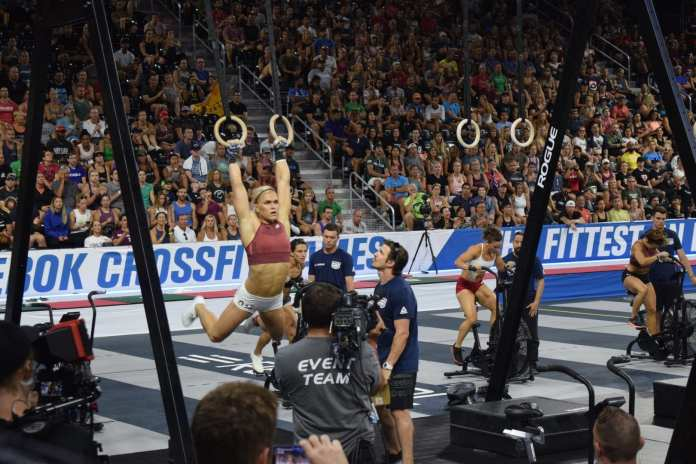 Katrin Davidsdottir on rings in the coliseum completing toes-to-rings in the 2019 CrossFit Games.