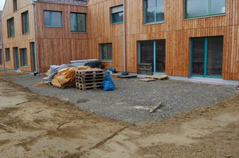 Terrasse zwischen Gemeinschaftsküche, Kräuterspirale, Griller und Lagerfeuerplatz