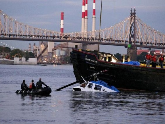 Rescue divers watch the helicopter that crashed into the East River with five people aboard after taking off from the 34th street helipad in New York
