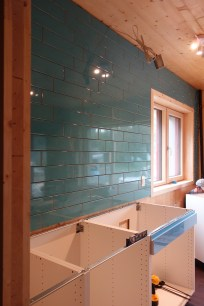 Turquoise tiled kitchen wall above fitted cabinets