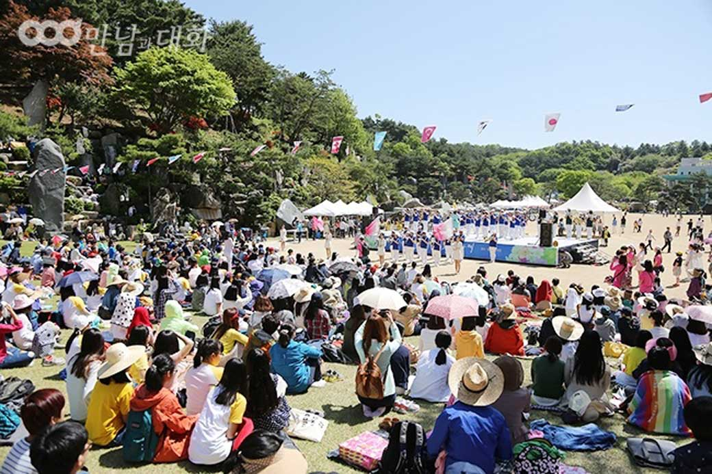 A crowd of people sit on the lawn sanctuary in Wolmyeongdong in participation of the Children's Day opening ceremony