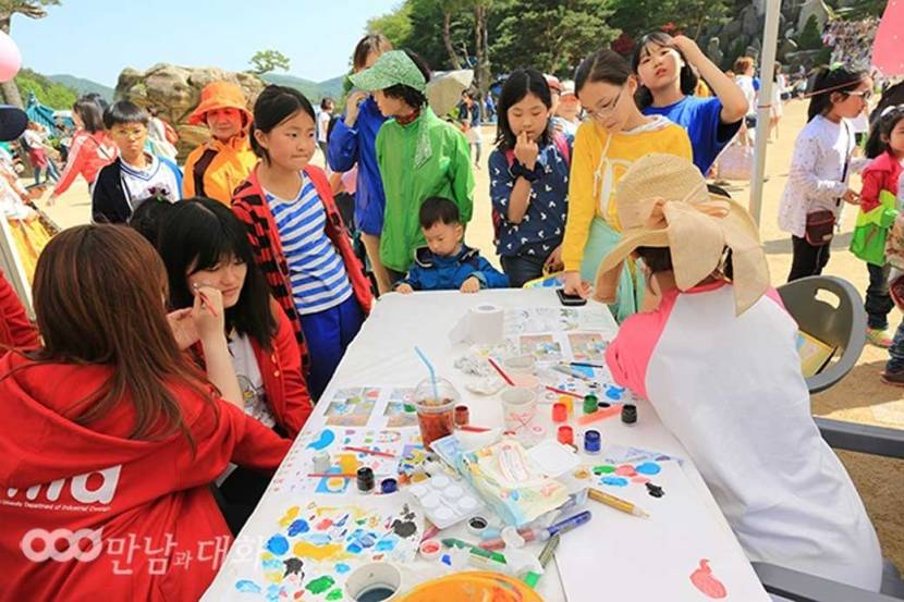 Children gather around an art table for face painting in the sports field of Wolmyeongdong