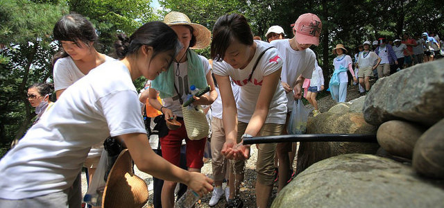 A group of hikers drink water from a natural water spring in Wolmyeongdong