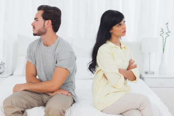 Couple sulking with arms crossed in bedroom