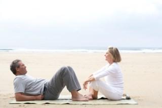 Mature couple on mat on beach, man reclining, woman sitting, side view