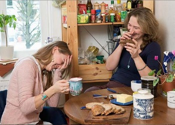 two women at tea laughing
