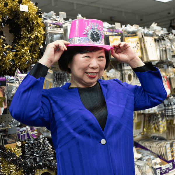 Wendy Shen standing in a store holding a pink hat on top of her head.