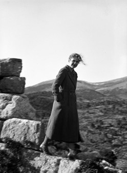 Agnes Newhall Stillwell in Eleutherae. She is seen standing next to some large stones. Rolling hills can be seen in the background.