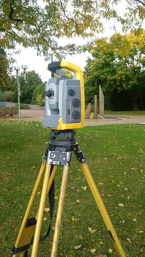Image of a yellow and grey machine set up on the grass.  The machine is a total station and a concrete sculpture can be seen in the background.
