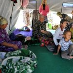 Ethnic Uzbek women and children sit in tent at the Kyrgyz-Uzbek border