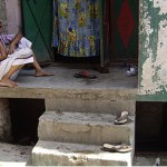 Poor and elderly woman sits outside sanitation facility