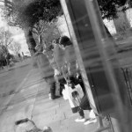 Woman standing on the street with young guys in a blur.