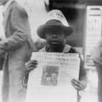 African American boy selling newspaper in 1921