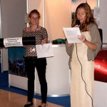 Two women are prepared to speak on a microphone