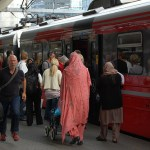Mutlitcultural people get on a train in Oslo, Norway.