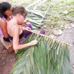 Bribri woman teaches guess to weave palm leaves